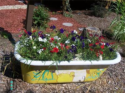 Rub a dub dub a bountiful amount of flowers in a cast iron tub. Cast iron tub of flowers.