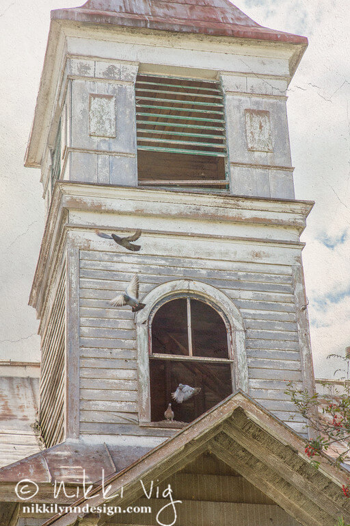Doves flying out of an old church dormer. Photography art prints for sale.