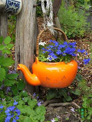 If you can find a vivid tea kettle with a handle they look mighty sweet hanging on garden posts, decks, and fences. Plant flowers of the opposite side of the color wheel as the teapot's color. This makes a BOLD visual statement in a flower garden.